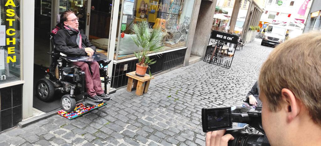 Julian Wendel testet mit seinem E-Stuhl unsere erste ausgelegte Legorampen vor dem Café Maincake in der Würzburger Altstadt.