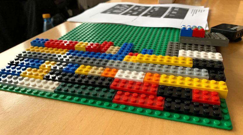 Bunte Legosteine auf einer grünen Grundplatte, die zu einer Legorampe verbaut werden.
