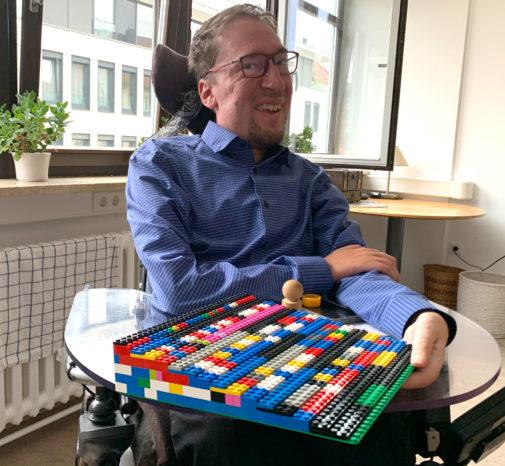 Julian Wendel im E-Rolli mit 1. Legorampe für Würzburg in der Hand